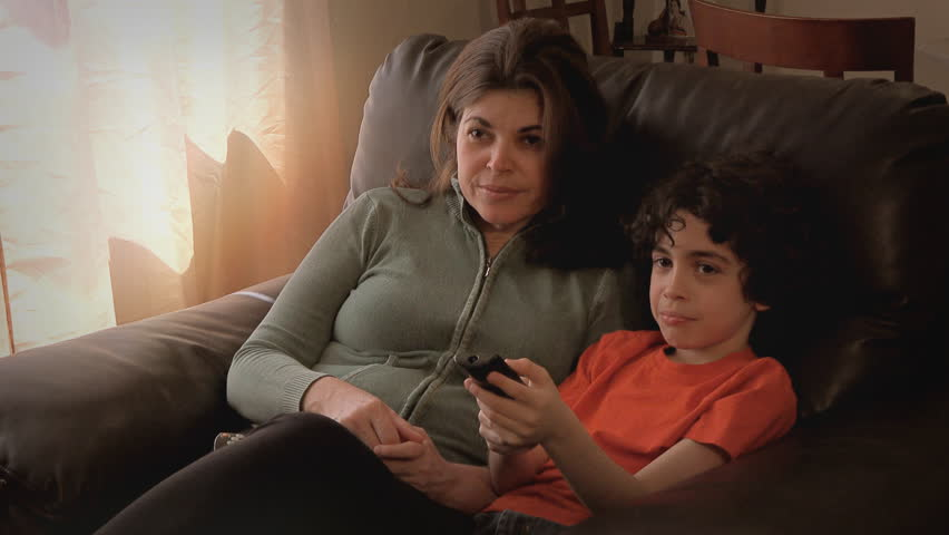 Single mother and child boy, small family watching TV in house living room and changing channels with a control remote.Stock footage in 4k uhd. - 4K stock video clip