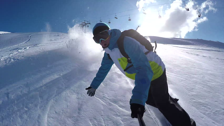 CLOSE UP: Snowboarder riding powder on a sunny winter day