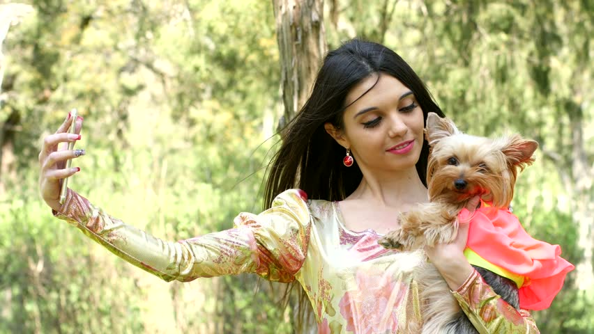 Lovely girl in park with dog in hand doing selfie via iphone - 4K stock video clip