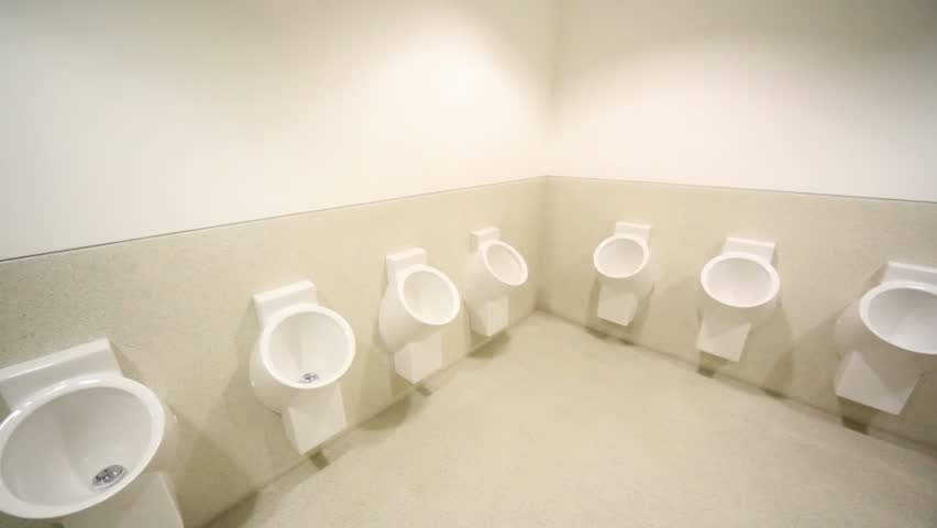 panning of empty mens toilet with row of urinals