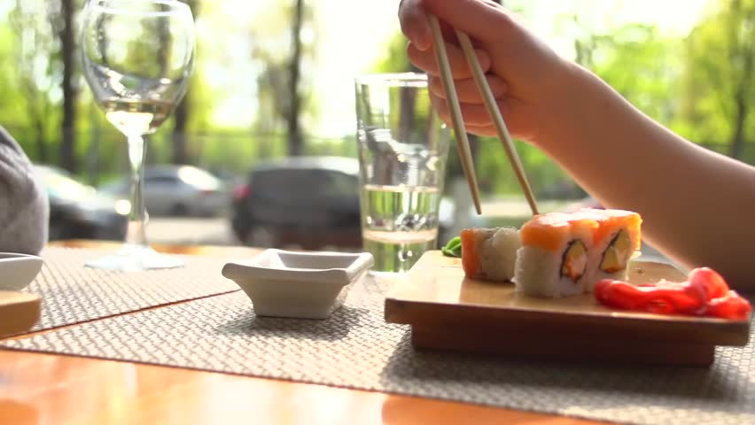 Young woman eating sushi rolls in a restaurant full hd for Japanese eating table