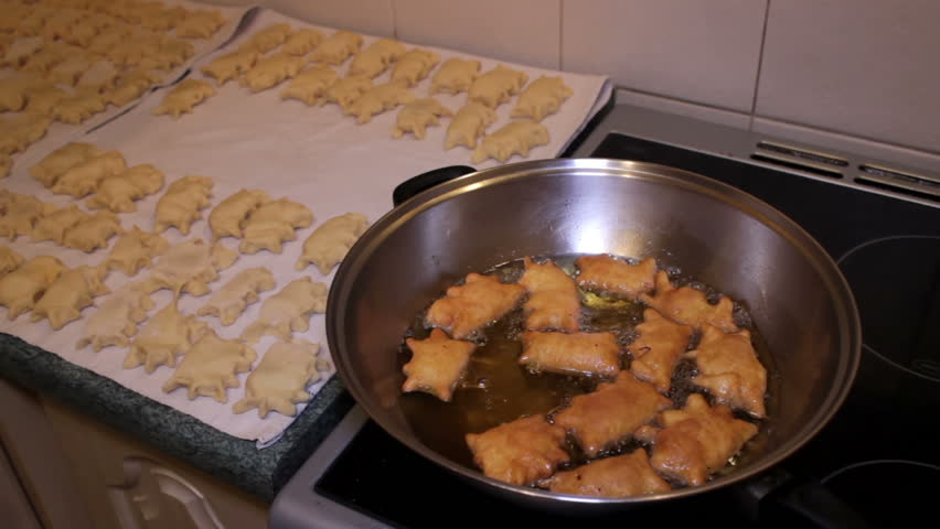 Traditional Food - deep oil fried pierogies stirring with a slotted spoon.