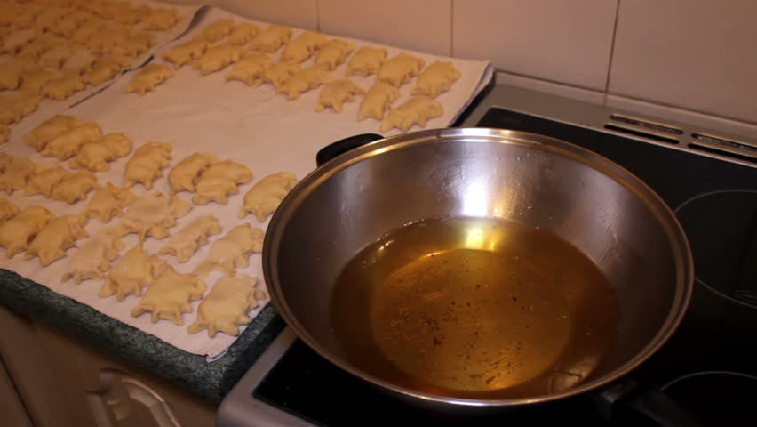 Traditional Food - male throws pierogies into hot, boiling oil.