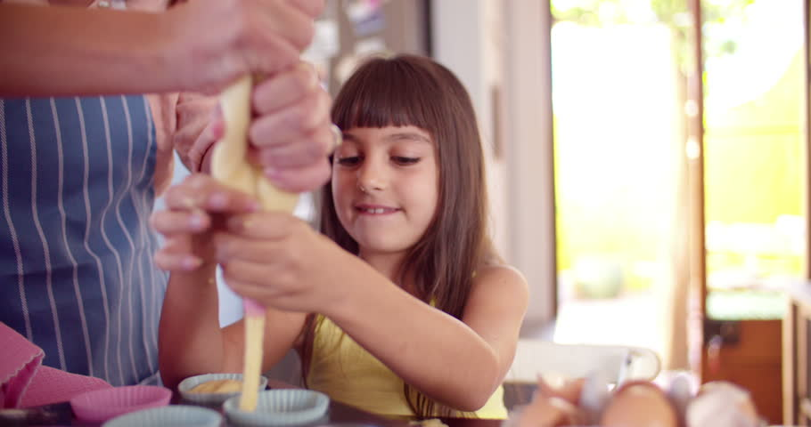 Cropped shot of a little girl and her mom squeezing dough into cupcake holders while making cupcakes together - 4K stock footage clip