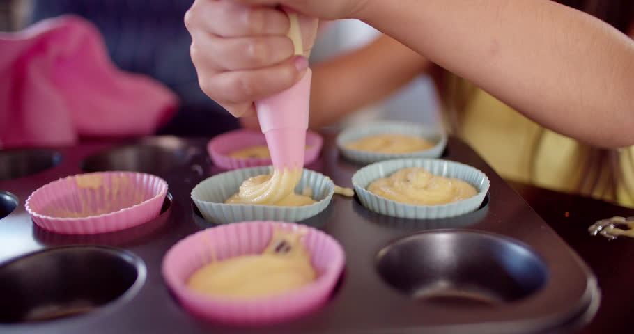 Cropped shot of a mom and daughter in the kitchen squeezing cupcake dough into cupcake holders in a baking tray, Slow Motion - 4K stock video clip