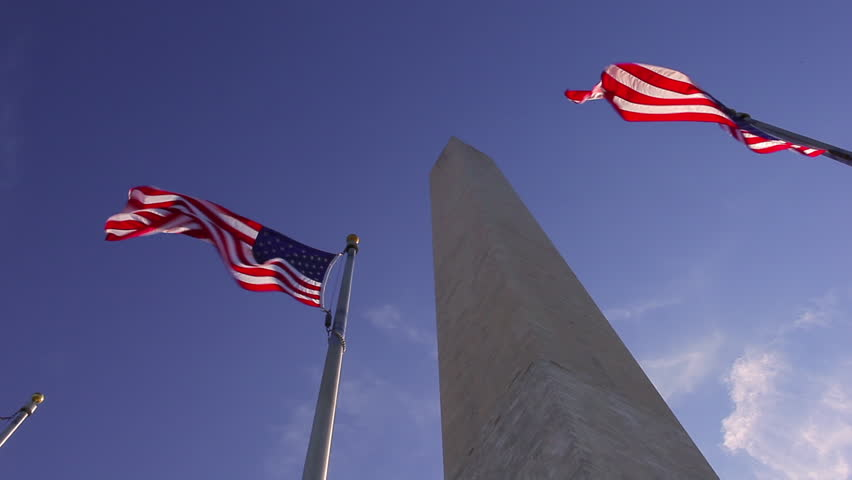 Washington, DC/United States - November 2012: A static shot of two american flags waving in the wind in front of the Washington Monument. - HD stock footage clip