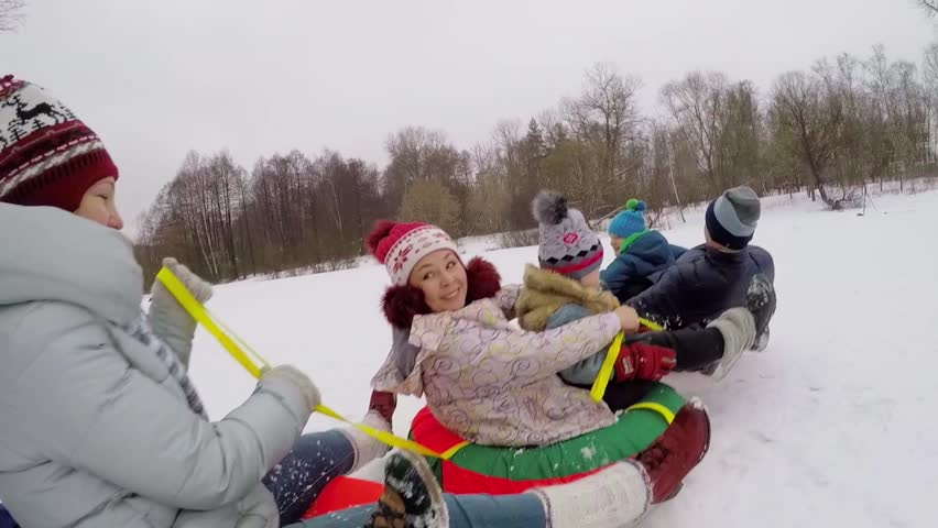 Six people ride on top of inner tubes by snow at winter day. Aerial view - HD stock footage clip