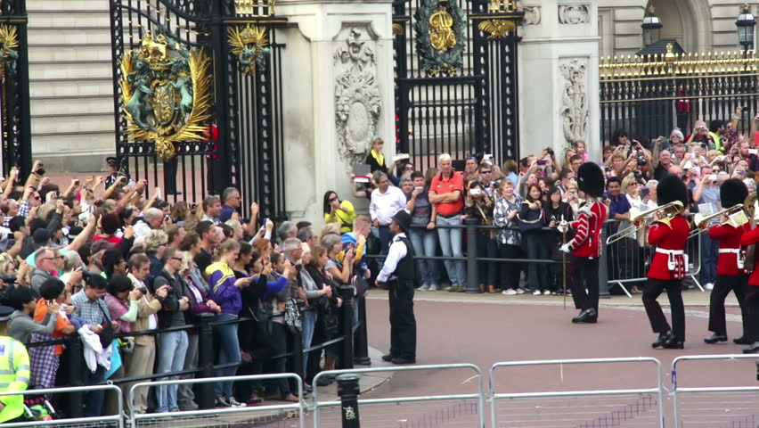 LONDON - CIRCA SEPTEMBER 2014, Buckingham Palace London Changing of the guard platoon enters Buckingham Palace gates marching and playing instruments with watching crowds, September 2014 - HD stock video clip