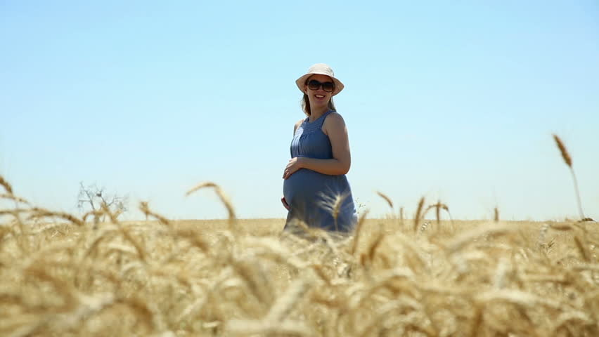 Young woman touching her pregnant belly on the middle of wheat field.