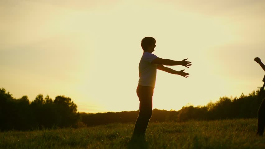 Romantic young couple silhouette. Woman is running to her man, they hug and spin around on a sunset with sun shining bright behind them on a horizon. Slow motion filmed at 240 fps. - HD stock video clip