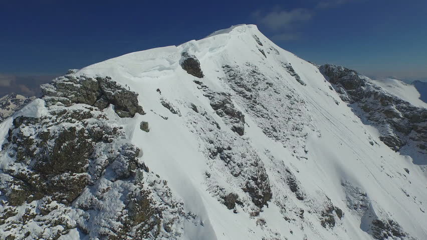 4k winter footage, aerial snow covered rocky mountain ridge