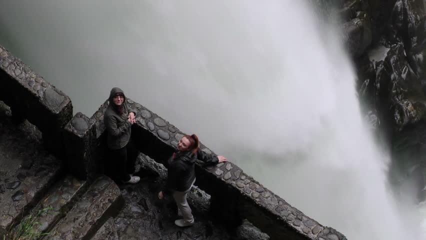 Adult women's tourists waving at the camera on Pailon del Diablo waterfall, popular tourist destination in Ecuador - 4K stock footage clip