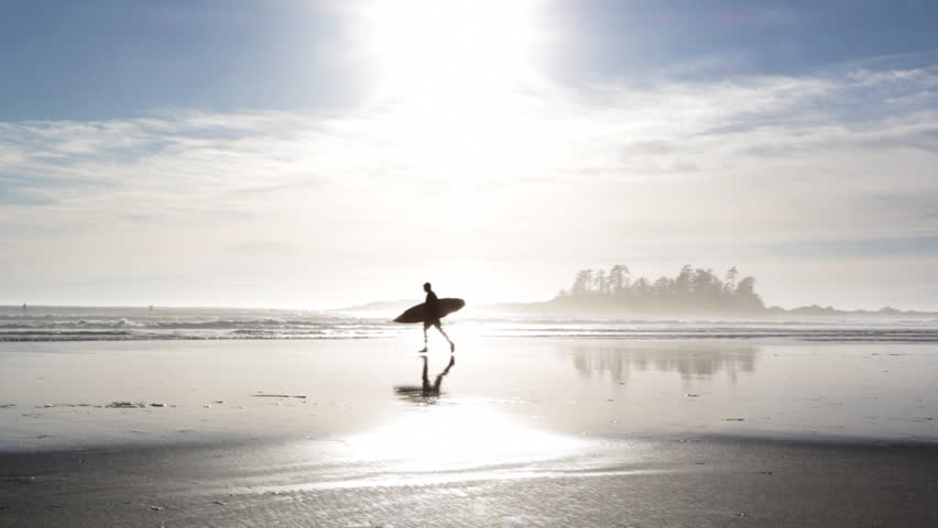 Surfer runs across beach. Silhouette of surfer running with surfboard. Reflection in the sand. Tofino, British Columbia, Canada.